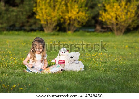 Little girl reading a book with her toys on the beautiful green lawn - stock photo
