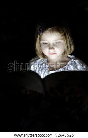 Little girl reading book in dark with light shining on face - stock photo
