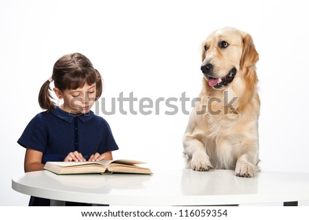 little girl reading with her golden retriever