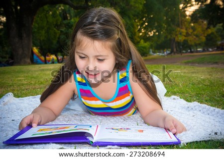 Little girl reads book lying on the green grass in the summer pa - stock photo