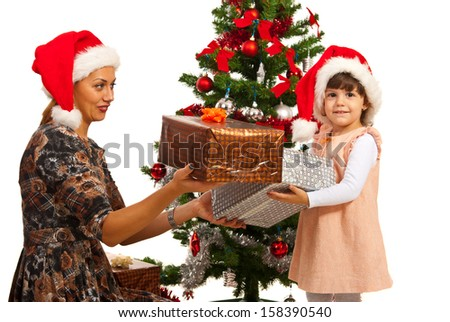 Little girl receive Christmas gifts from her mother - stock photo