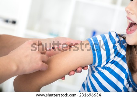 little girl receiving injection  with a smile. - stock photo