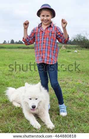 Little girl rejoices while standing on green grass with laying beside white dog