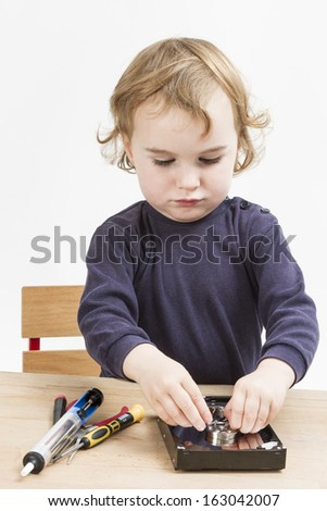 little girl repairing computer parts. studio shot with neutral grey background