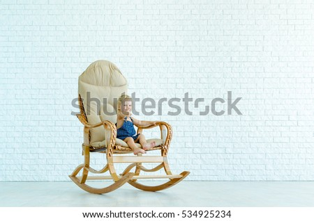 Little girl rides a rocking chair on the background of a white brick wall.