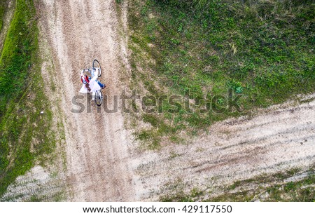 little girl rides bicycle in helmet on country road, top view