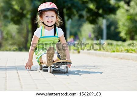 Little girl rides down park alley sitting on skateboard - stock photo