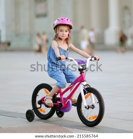 Little girl riding a bike in a city - stock photo