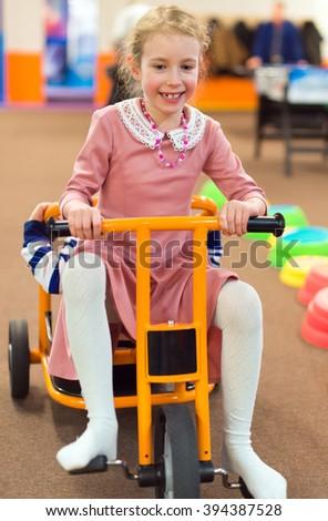 Little girl riding bicycle in kindergarten. - stock photo