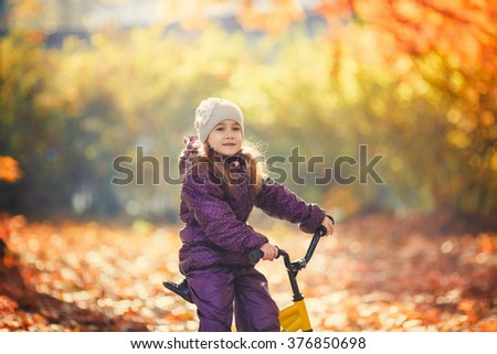Little girl riding her bicycle in the autumn park.