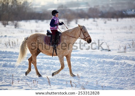 Little girl riding horse in rural environment in winter - stock photo