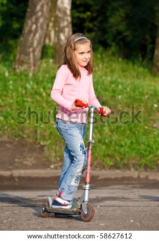 Little girl riding in the park on scooter