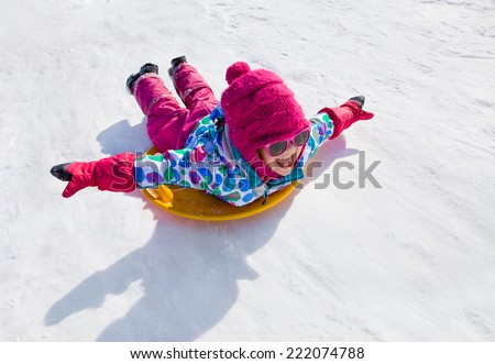 little girl riding on snow slides in winter time - stock photo