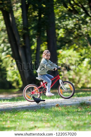 Little girl riding red bike in fall park. - stock photo
