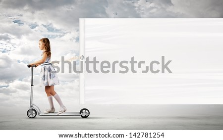 Little girl riding scooter and pulling blank banner