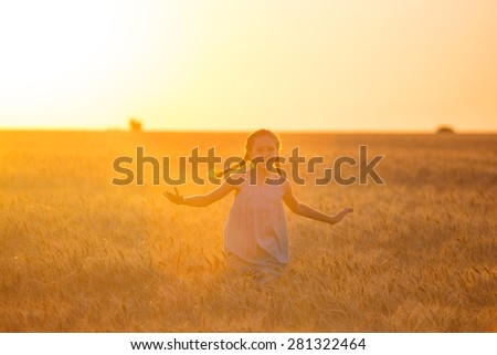little girl running at the orange evening wheat field 