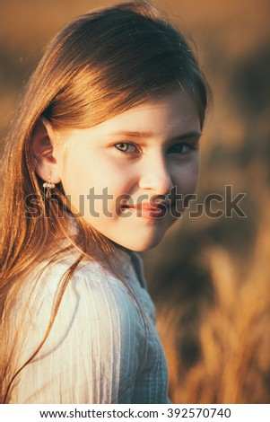 little girl running at the orange evening wheat field - stock photo