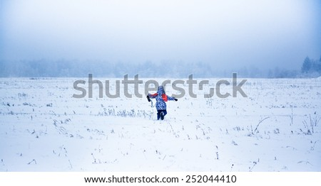 Little girl running away in a snowy park - stock photo