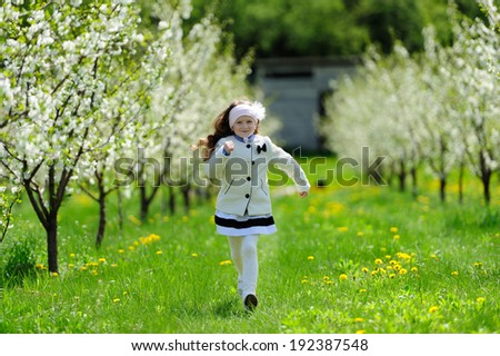 little girl running in the blooming  garden - stock photo