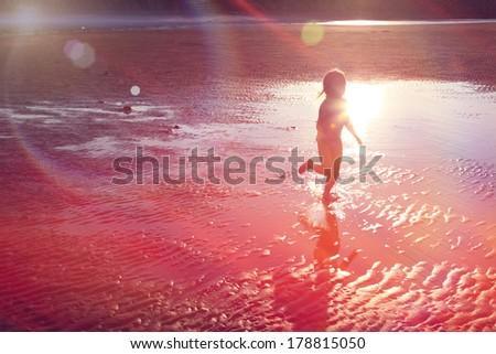 Little Girl running on beach in Sunlight - stock photo