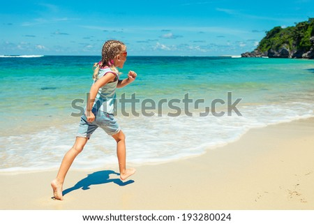 little girl running on the beach in the day time