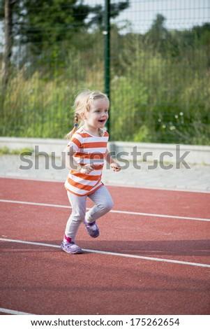 little girl running on the treadmill - stock photo
