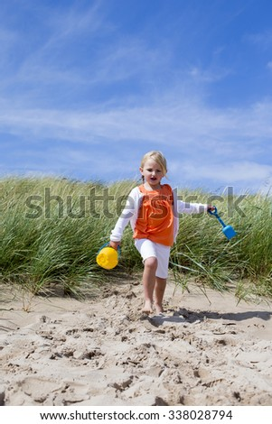 Little Girl running onto the beach with her arms outstretched and holding a bucket and spade.  - stock photo