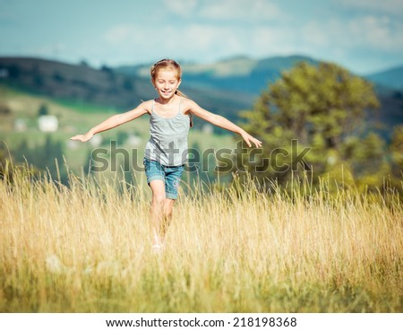 little girl runs through a beautiful meadow in the mountains. - stock photo