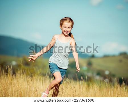 little girl runs through a meadow in the mountains. - stock photo