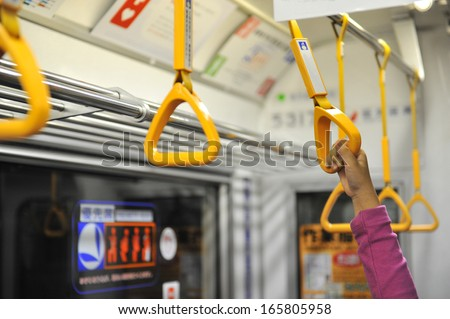 Little girl's hand holding subway strap during transportation