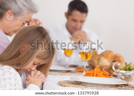 Little girl saying grace with family before thanksgiving dinner - stock photo