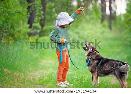 Little girl schooling dog in the forest - stock photo