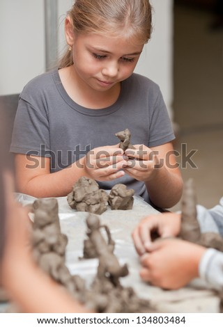 Little girl sculpts a toy from clay with enthusiasm - stock photo