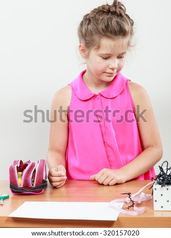 Little girl searching for her accessories in the classroom. Being creative in elementary age