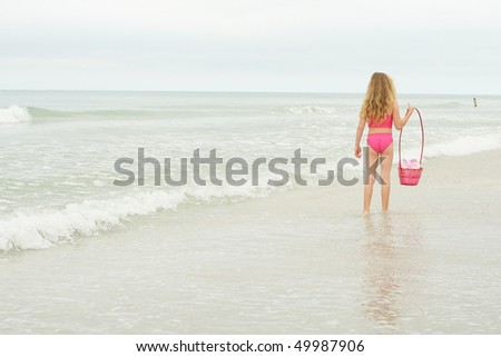 little girl searching for shells - stock photo