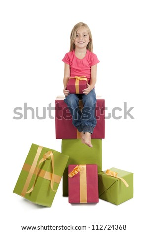little girl seated on a stack of birthday presents, isolated on white background - stock photo