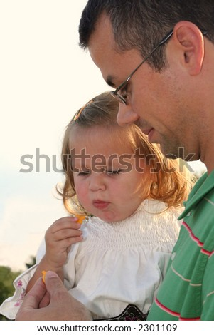Little girl sharing a snack of crackers with her father. - stock photo