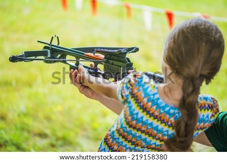 Little girl shooting crossbow at summer outdoor shooting range. - stock photo