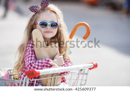 Little girl shopping with cart and bags. Child sitting in shopping cart near mall. Happy smiling child sitting in trolley cart. Sales and shopping