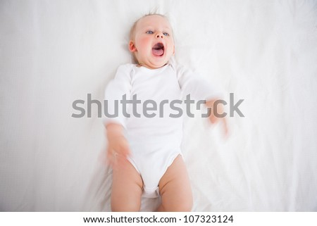 Little girl shouting while lying on a blanket indoors - stock photo