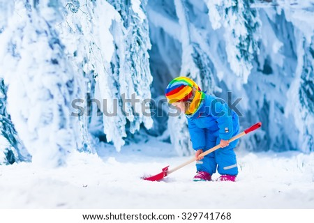 Little girl shoveling snow on home drive way. Beautiful snowy garden or front yard. Child with shovel playing outdoors in winter season. Family removing snow after blizzard. Kids play outside. - stock photo