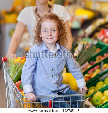 Little girl showing apple with mother in background at grocery store - stock photo