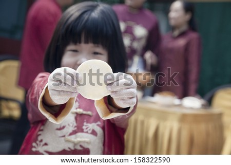 Little girl showing dumpling wrapper in traditional clothing - stock photo
