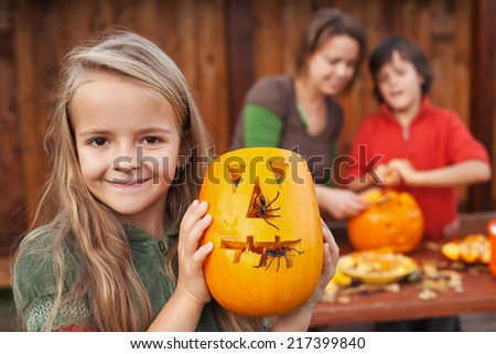 Little girl showing her freshly carved Halloween jack-o-lantern - stock photo
