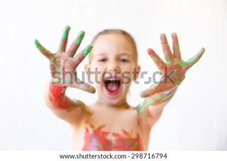 Little girl showing her hands, covered in finger paint after painting a picture and her body with it. Sensory play, permissive upbringing, fun childhood concept, selective sharpness.  - stock photo