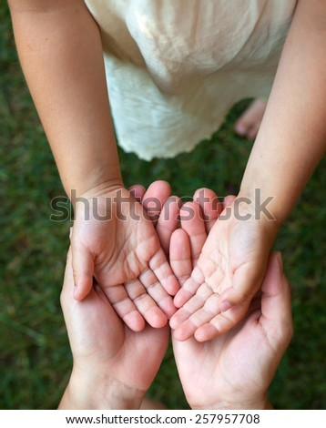 Little girl showing her hands to mother outdoors - stock photo