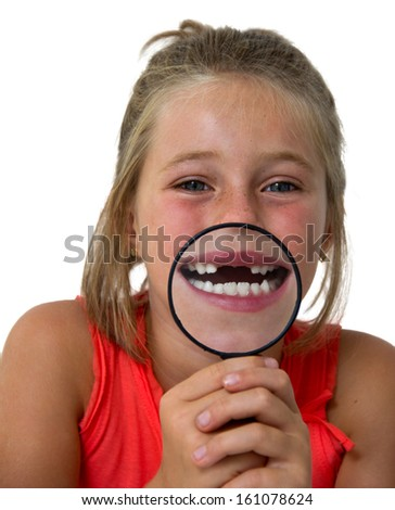 little girl showing her mouth through a magnifying glass - stock photo