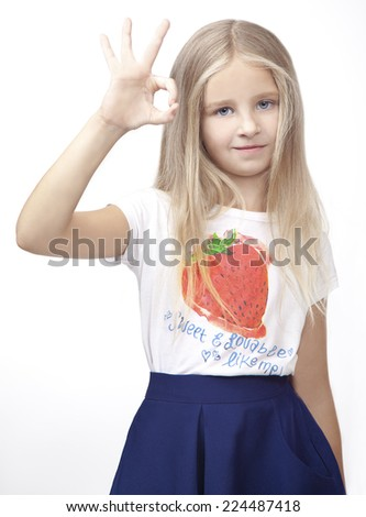Little girl showing okay, she wearing a T-shirt with a strawberry. Isolated on the white background. - stock photo