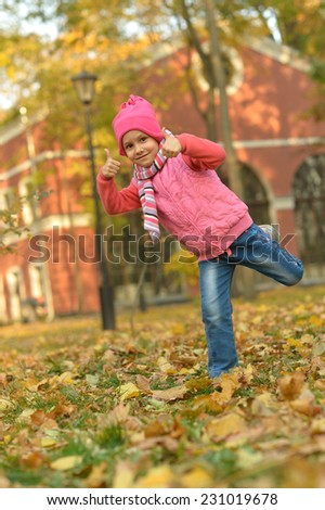 Little Girl showing thumb up in autumn park