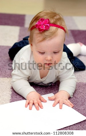 little girl shows a paper sheet